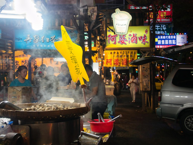 Peanuts being roasted in steaming big pan at taiwanese night market RuiFeng in Kaohsiung, Taiwan