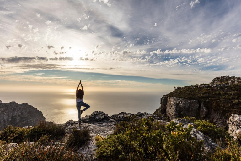 Woman doing yoga on a Table Mountain, Cape Town