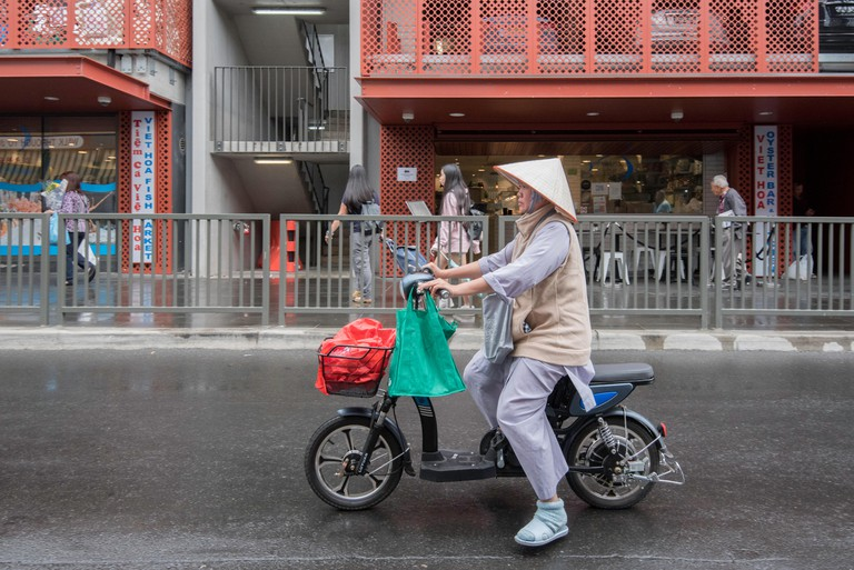 A woman riding an electrical bicycle in the Sydney suburb of Cabramatta