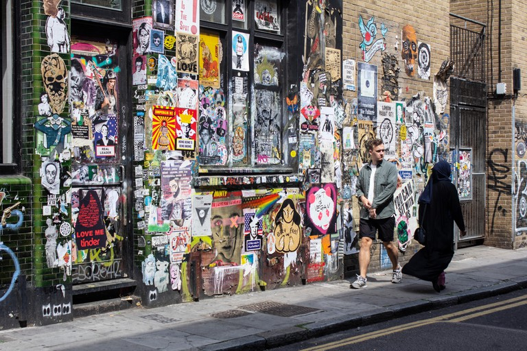 Walls with graffiti and posters in Brick Lane, London
