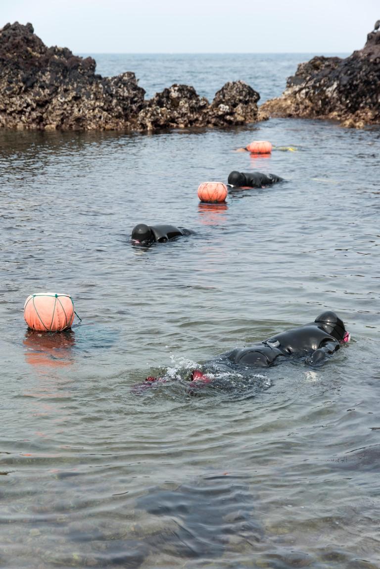 Haenyeo Swimming In Sea Against Clear Sky At Jeju Island