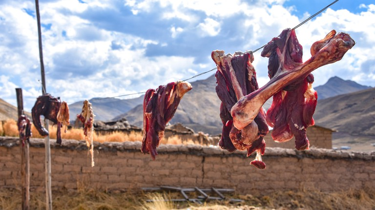 Alpaca meat and bones hang to dry on a washing line in rural Cusco, Peru