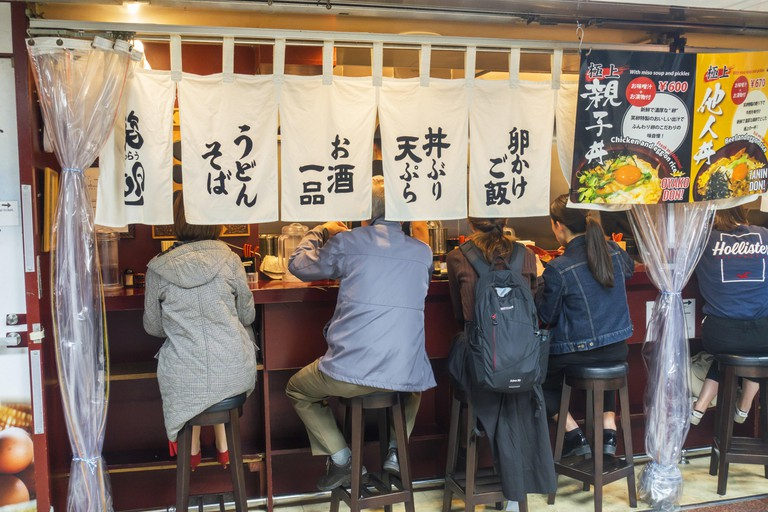 Osaka, Japan - November 3rd, 2019:People eating in Izakaya, a type of informal Japanese pub and casual place for after-work drinking.