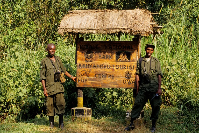 Rangers stand near a sign for Kanyanchu Tourist Centre