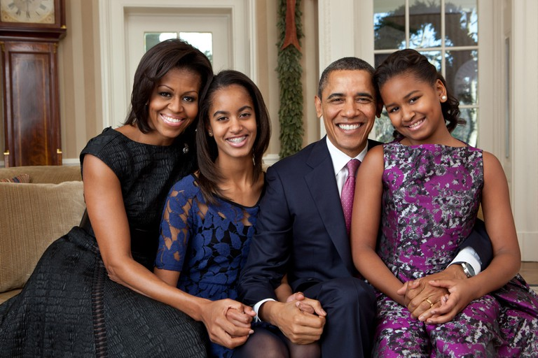 President Barack Obama, First Lady Michelle Obama, and daughters, Sasha and Malia, sit for a family portrait in the Oval Office