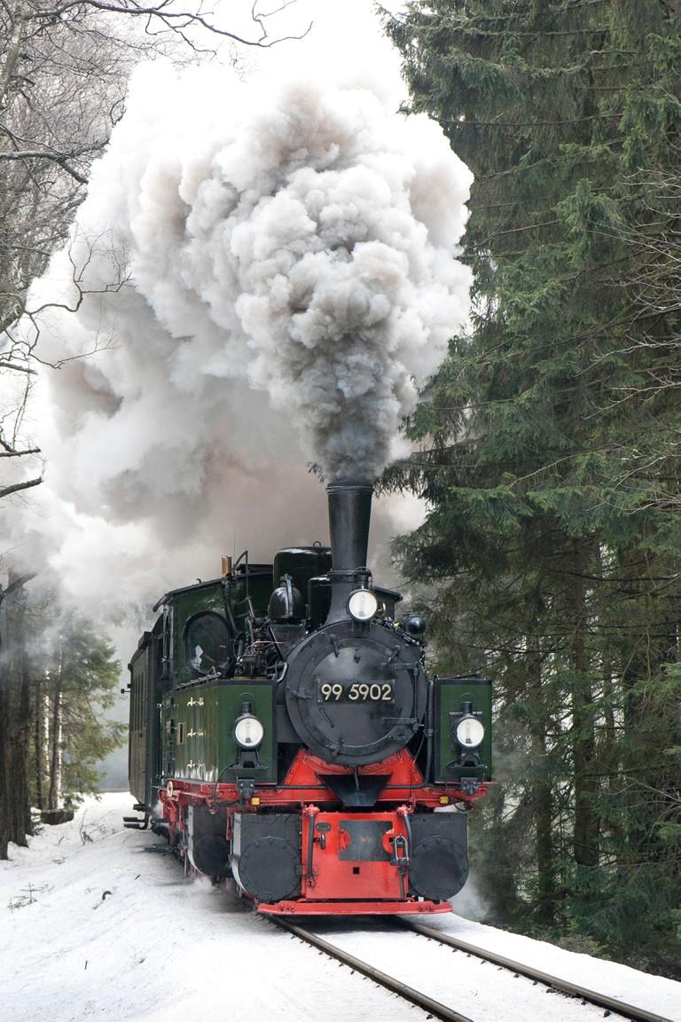 A steam locomotive with a passenger train on the Harz Mountain Railway near the Brocken