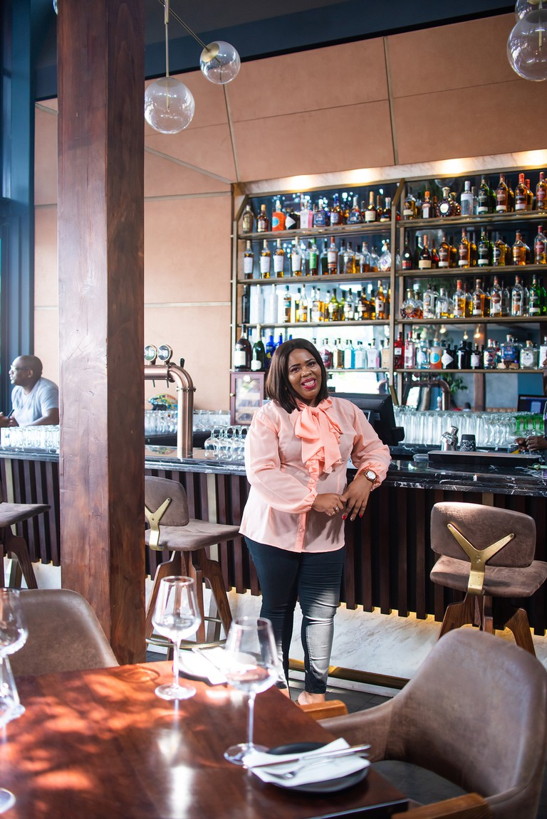 Thandi standing in front of the Dukkah restaurant bar, Durban, South Africa, 2020.