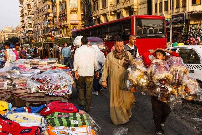Street trade, traffic and passers-by in Midan Ataba where downtown and Islamic Cairo meet. Egypt