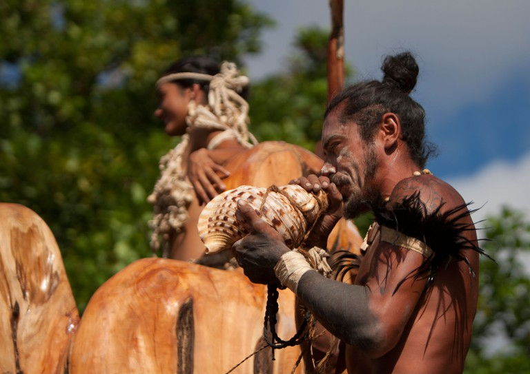 Warrior blowing a shell during Tapati Festival