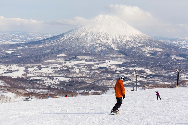 Snowboarders on the ski slopes of Niseko Annupuri overlooking Mt Yotei