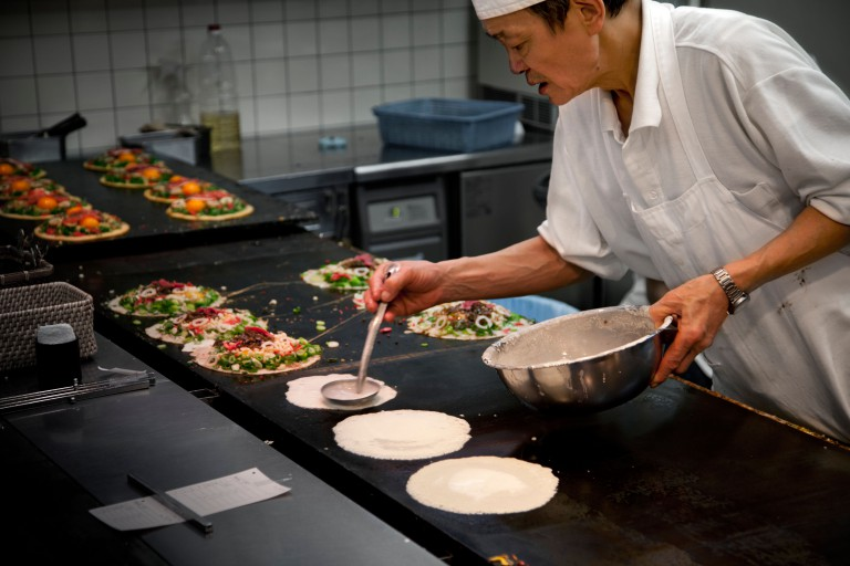 Japanese chef making traditional okonomiyaki pancakes in Japan