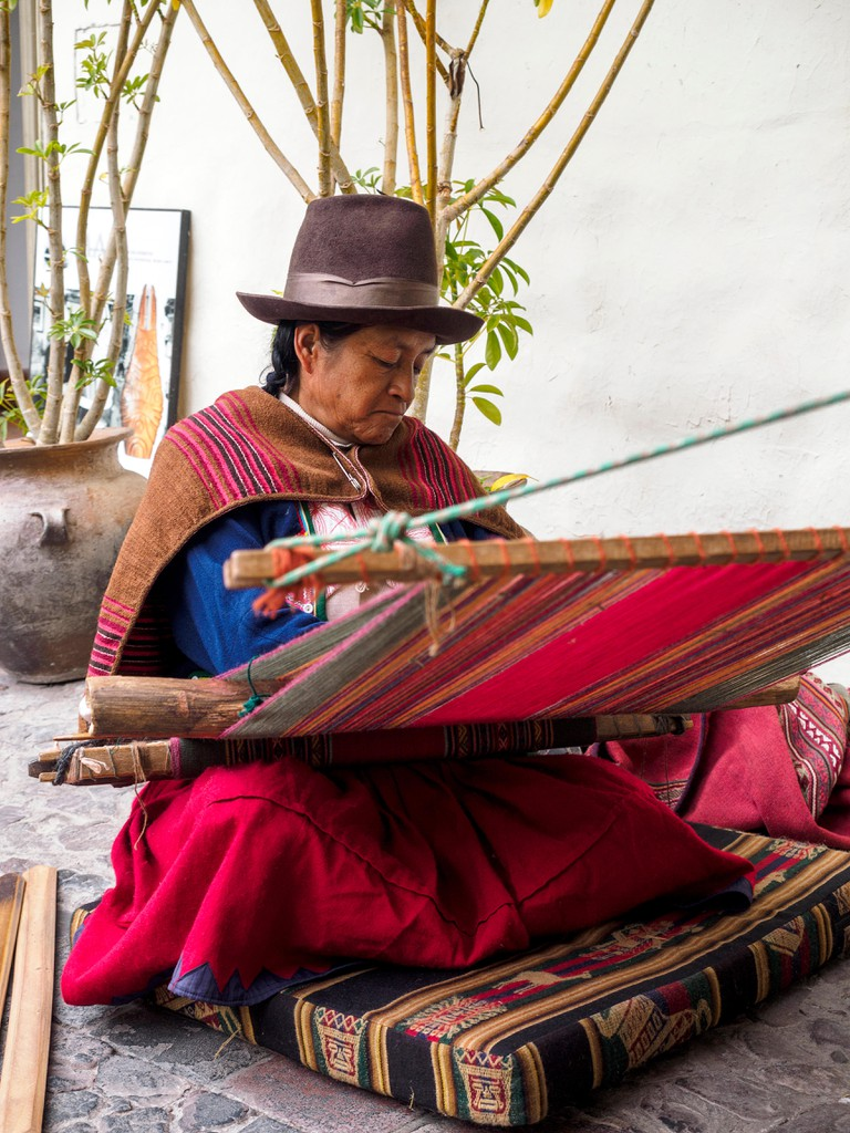 Quechua Indian woman weaves with a strap loom inside the Pre-Columbian Art Museum - Cusco, Peru