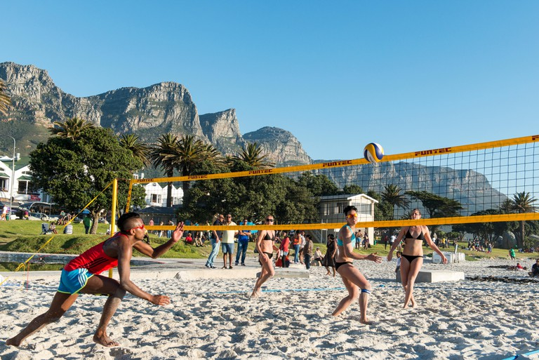 Beach volleyball players on the beach of Camps Bay, Cape Town