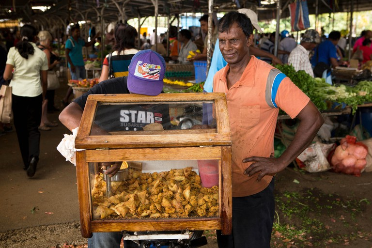 Mauritius, Quatre Bornes, snack seller selling samosas and pakoras from box on bicycle