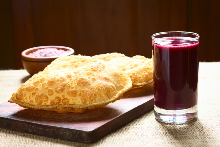 Traditional Bolivian snack called Pastel (deep-fried pastry filled with cheese) served with Api, a purple corn beverage. Image shot 2014. Exact date unknown.