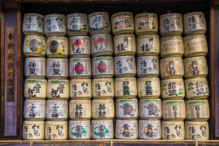 A collection of Japanese sake barrels stacked on top of each other in Heian Shrine, Kyoto, Japan