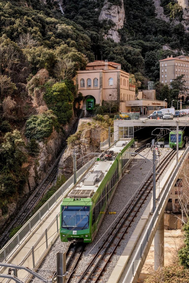MONTSERRAT, SPAIN - MARCH 06, 2012: Rack railway train departing Montserrat Cremallera station near monastery on March 06, 2012