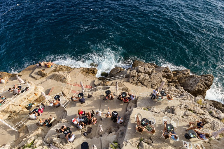 People sitting at the Buza Bar in Dubrovnik, Croatia, viewed from above.