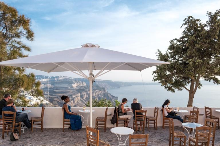 Greece, Santorini island, Fira, tourists in a coffee bar on caldera pathway