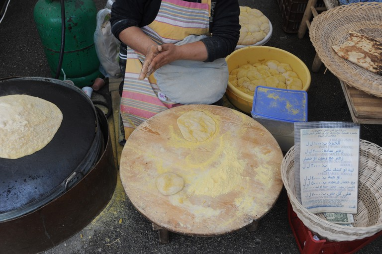 Lebanese bread being prepared on a stove in el Tayeb market