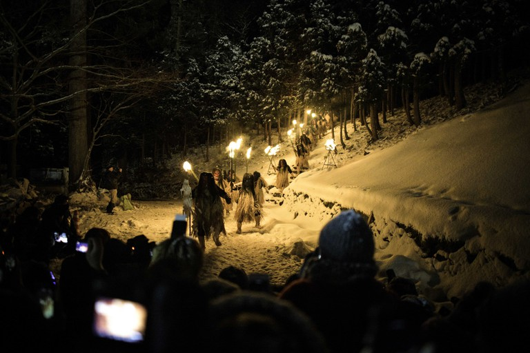 Men dressed in straw clothes and orge masks as Namahage, or mountain demons, march down from a snow mountain with flaming torches during the Namahage Sedo Festival