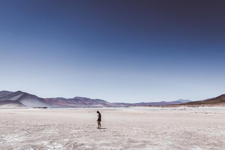 Woman walking at salt flat in Atacama desert