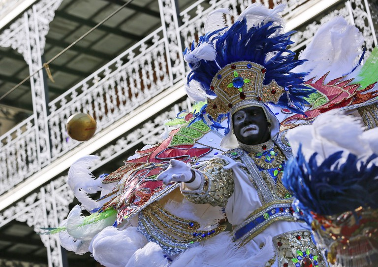 A member of the Zulu throws a coconut during Mardi Gras day in New Orleans, Louisiana.