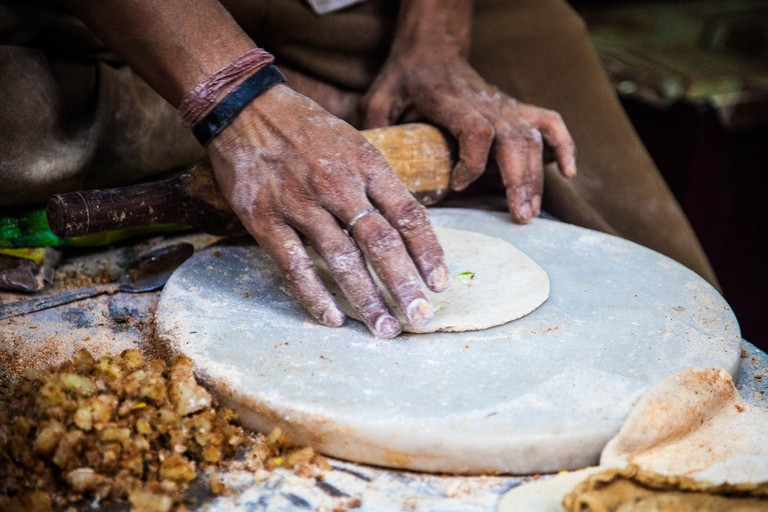 On an Old Delhi street, a man is making parathas.