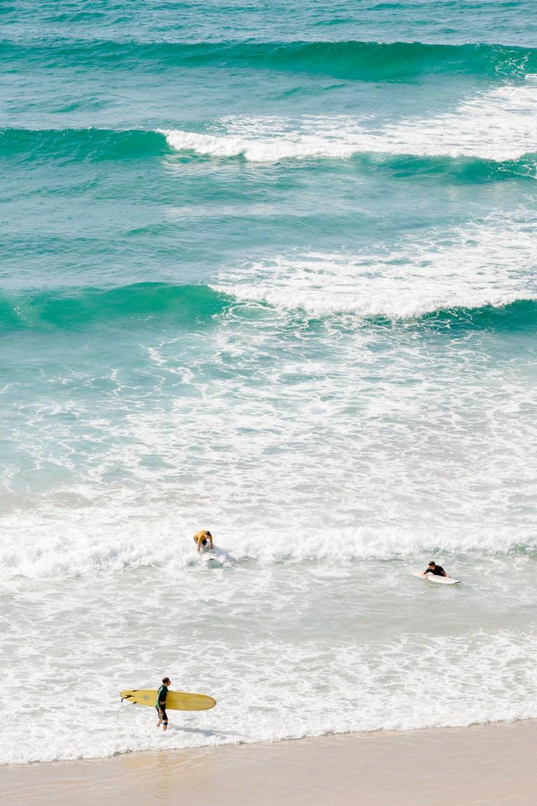 People surfing at Wategos Beach in Byron Bay.