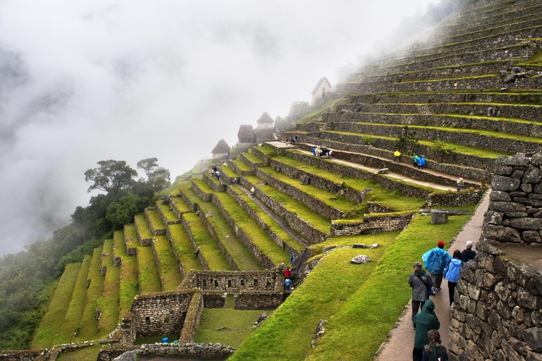 Terraces inside the archaeological complex of Machu Picchu. Machu Picchu is a city located high in the Andes Mountains in modern Peru. It lies 43 miles northwest of Cuzco at the top of a ridge, hiding it from the Urabamba gorge below. The ridge is between