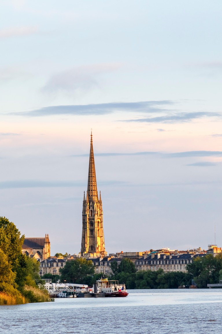 Evening view of Bordeaux waterfront and spire of St Michael's Basilica by the Garonne River, in the wine-growing region of southwestern France