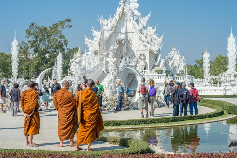 Buddhist monks at ornate Wat Rong Khun (White Temple) in Chiang Rai northern Thailand. This unconventional Buddhist temple is an ongoing project.