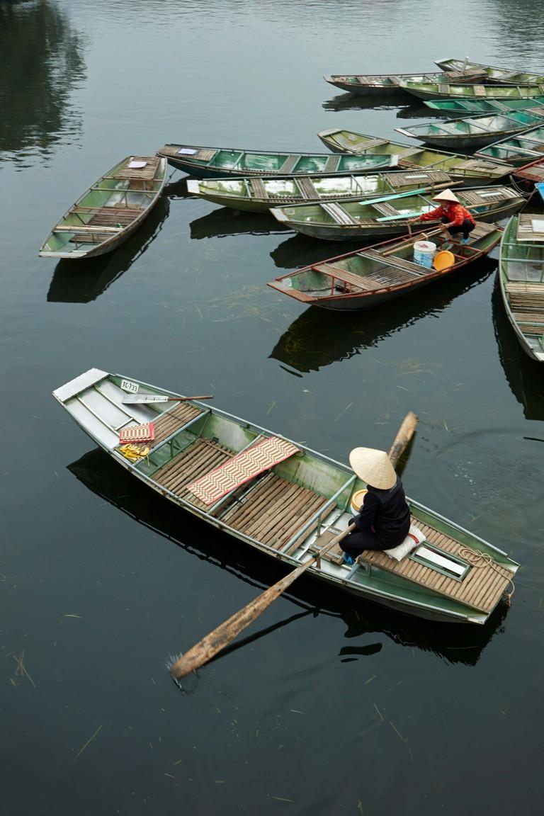 Woman in boat at Ninh Hai boat harbour for Tam Coc boat trips, Ninh Binh, Vietnam