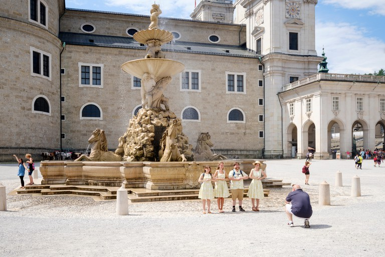 Tourists pose in Sound of Music costumes in Residenzbrunnen, Salzburg