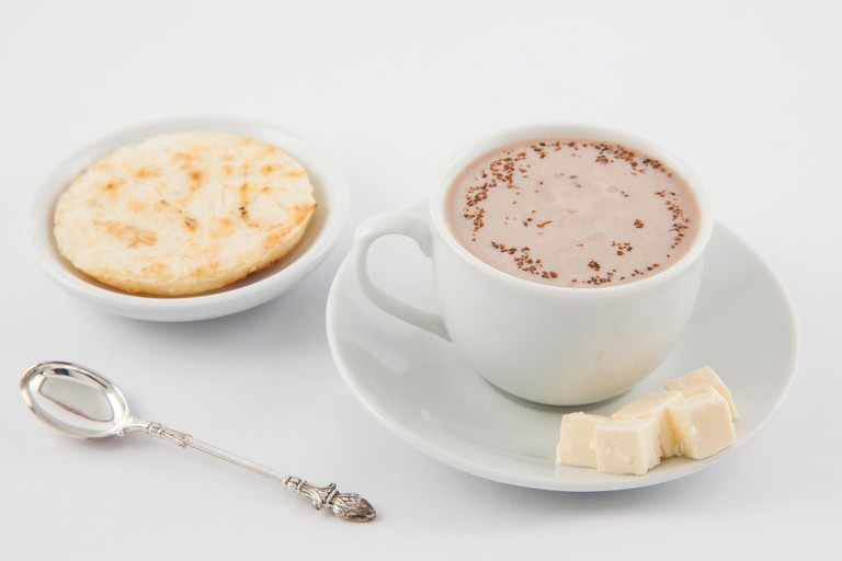 Cup of hot chocolate with cheese and arepa