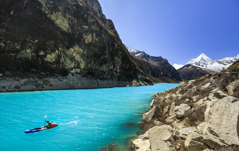 A man kayaking on Lake Paron in the Peruvian Andes.