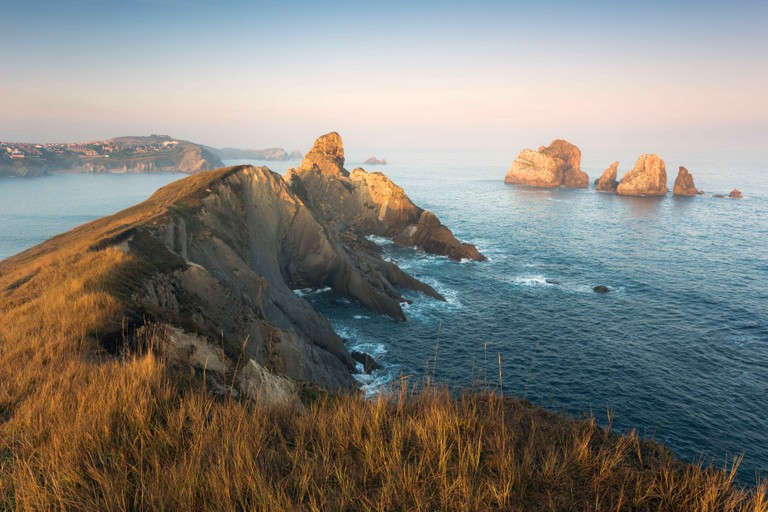 View over rugged coast at Santander / Liencres in first warm and soft morning light, Cantabria, Spain