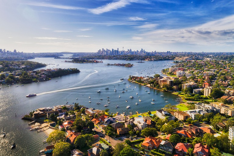 Sydney inner west suburb Drummoyne and beyond on shores of Parramatta river flowing into Sydney harbour with distant city CBD on horizon in elevated a