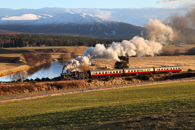 46512 heads along the Strathspey Railway  by fishermans crossing with the Cairngorm mountains behind.