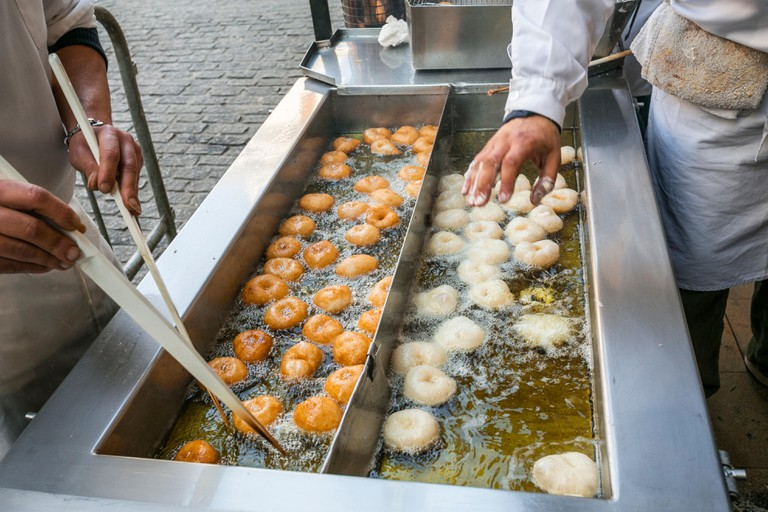Fallas festival. Cooking bunuelos,a typical Spanish Fritters. El Collado horchateria. Valencia. Valencian Community. Spain