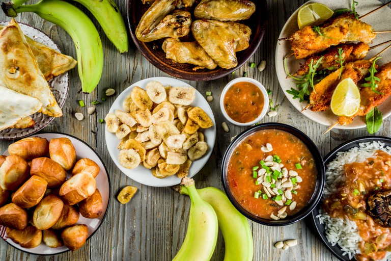 West african food concept. Traditional Wset African dishes assortment - peanut soup, jollof rice, grilled chicken wings, dry fried bananas plantains,
