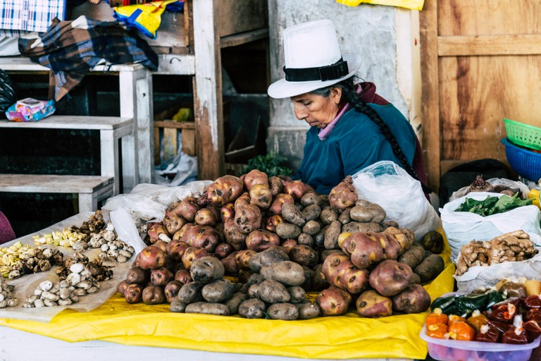 Peruvian woman sitting behind her stall in Mercado San Pedro (Cusco, Peru), selling potatoes, beans and other produce, wearing a traditional white hat.