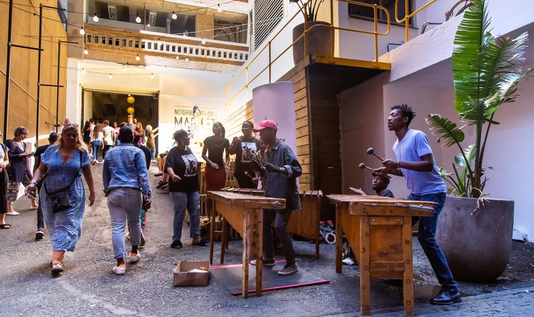Musicians perform outside the entrance to a food market