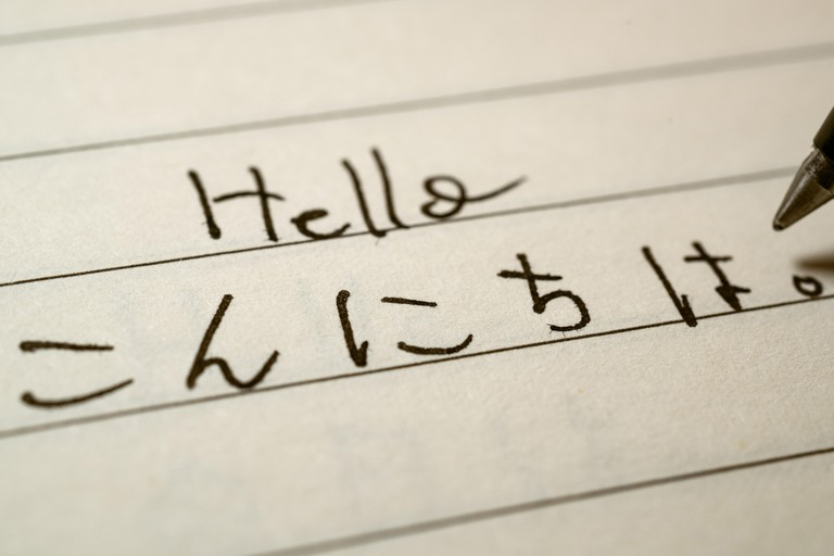 Beginner Japanese language learner writing Hello word in Japanese hiragana characters on a notebook close-up shot