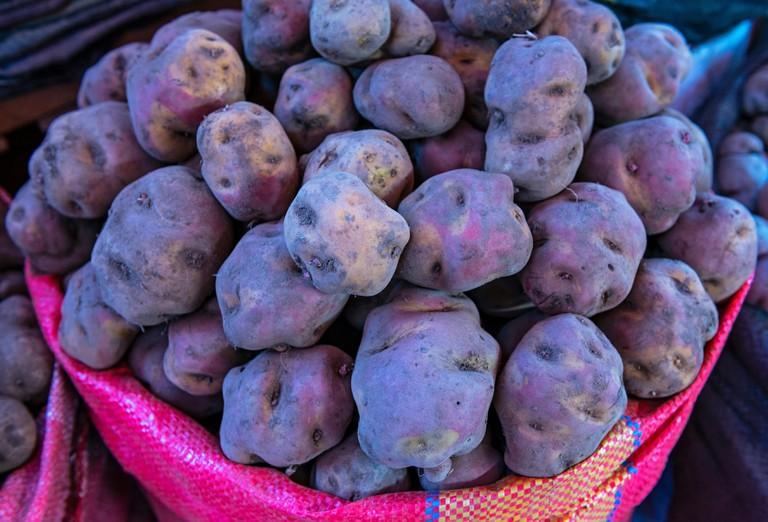 A pile of purple peruvian potatoes in a vegetable market in Cusco