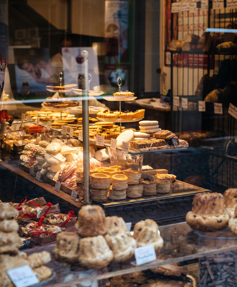 Lyon, France - Oct 27, 2017: View from the street of interior of traditional French bakery selling croissants, bread, cakes, tartes and multiple sweet and salty food