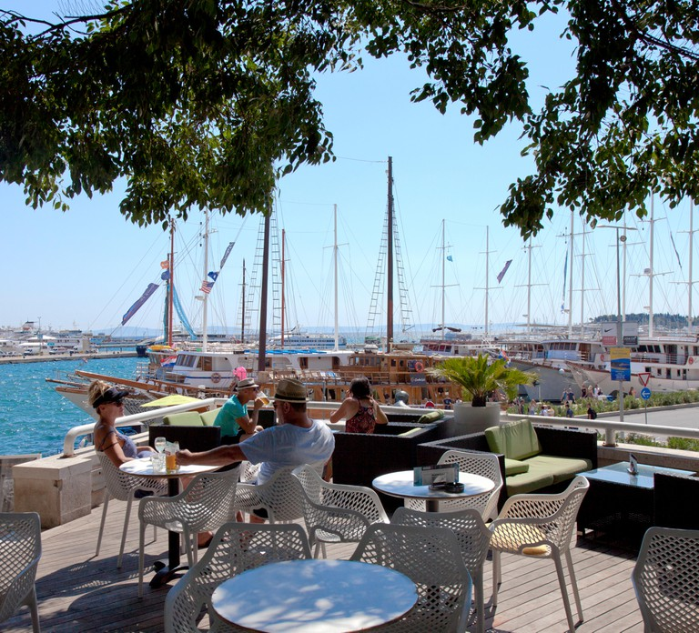 Unidentified people enjoying snacks on a restaurant terrace over looking Split, Croatia's harbor. Editorial use only.