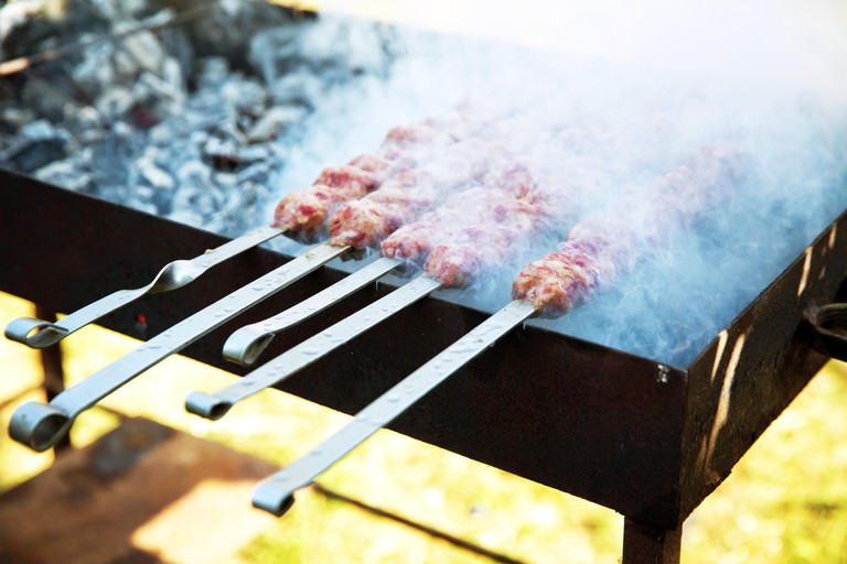 Lula kebab on skewers , traditional Caucasian dish, close-up . Appetizing lula kebab grilled on metal skewer. Cooking meat. Shish kebab on a metal