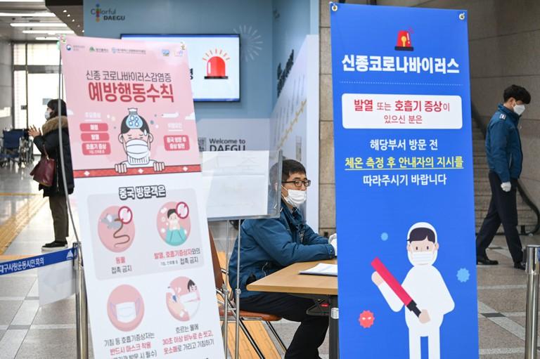 Signs show precautions for avoiding coronavirus inside City Hall while a guard waits in Daegu, South Korea