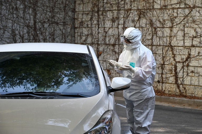 Health workers in biohazard suits treat patients at a drive-thru coronavirus testing center at Seoul Metropolitan Eunpyeong Hospital